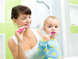 mother and little daughter brushing teeth in bathroom