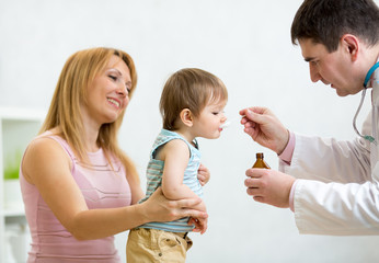 pediatrician giving spoon dose of medicine drinking syrup to