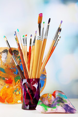 Paint brushes with paints and palette on bright background