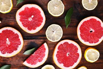Ripe slices lemon and grapefruit on wooden background