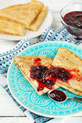 Plate of delicious pancakes with berry jam on wooden background