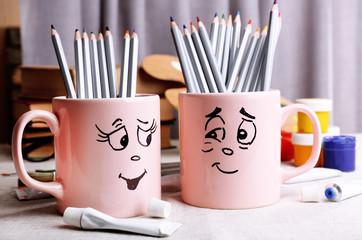 Emotional cups with pencils and paints on table