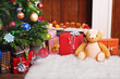 Teddy bear with Christmas gifts in room