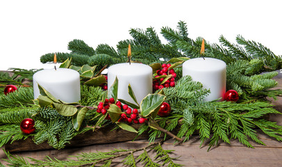 Burning white candles with boughs
