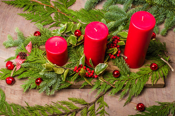 Three red candles in a Christmas arrangement