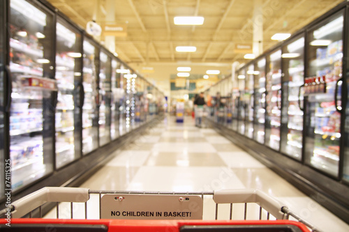 an aisle in a grocery store showing frozen foods - 74115325