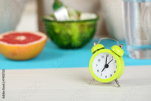 canvas print picture Alarm clock and dietary food on table close-up