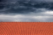 Dark rain clouds above the orange roof. - 74116394