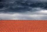 Dark rain clouds above the orange roof.