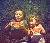 two kids eating watermelon done with a retro vintage instagram f