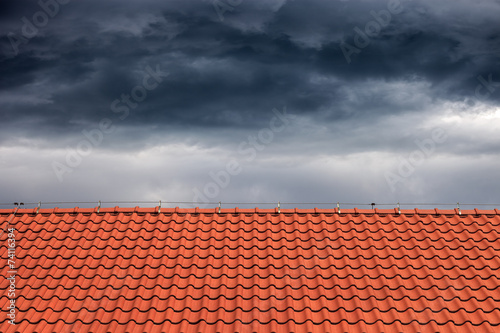 Dark rain clouds above the orange roof. - 74116394