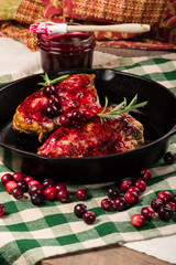 Cranberries and cast iron skillet with chicken