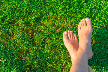 Men's feet on the background of lush green grass