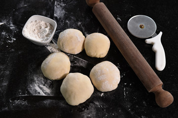 Small balls of fresh pizza dough on wooden board.