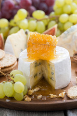 camembert with honey and fruit close-up on wooden tray