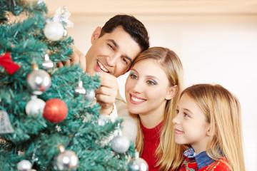 Familie beim Schmücken vom Weihnachtsbaum