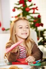 Mädchen verschenkt Glückwunschkarte zu Weihnachten