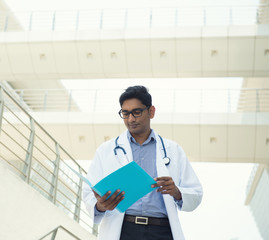indian male doctor reading report, slight vintage tone