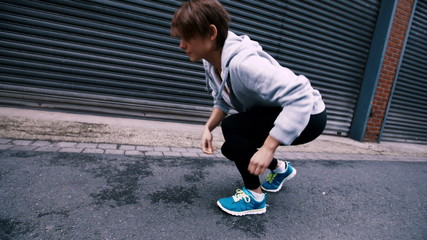 Runner Tying Shoelaces In Road starting to run