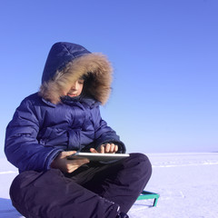boy outdoors with tablet PC in winter  time