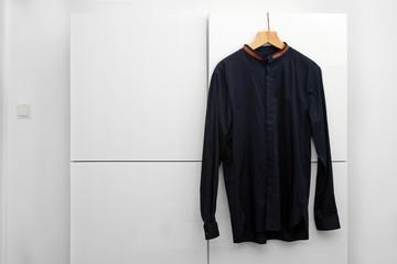 man's shirt hanging on a hanger in wardrobe