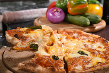 Close up of pizza and ingredients on wooden board.