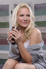 Attraktive Frau mit Kaffeetasse zuhause