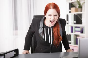 Junge Geschäftsfrau schreit vor Unzufriedenheit