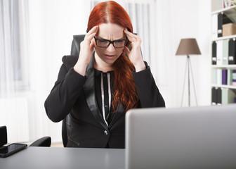 Junge Geschäftsfrau hat Kopfschmerzen am Schreibtisch