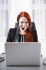 Junge Geschäftsfrau mit Headset vor ihrem Laptop