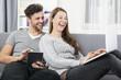 Junges glückliches Paar schaut lachend auf einen Laptop