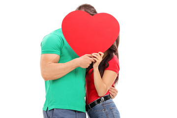 Young couple kissing behind a red heart