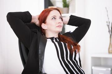Junge Geschäftsfrau lehnt sich zurück und überlegt oder träumt