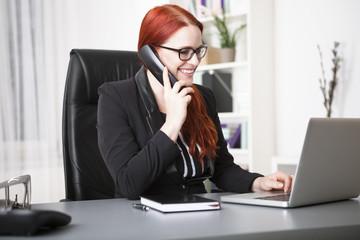 Junge lachende Geschäftsfrau telefoniert