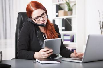 Junge Geschäftsfrau telefoniert und arbeitet mit dem Tablet