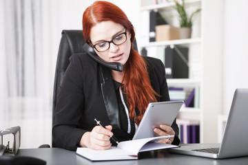 Telefonierende Geschäftsfrau mit Tablet schreibt Notizen
