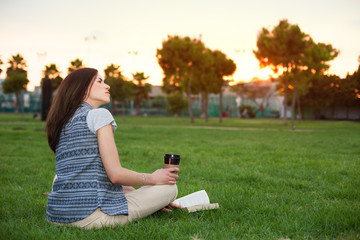 young and beautiful woman on the grass with a book