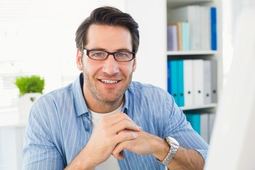 Editor working at his computer smiling at camera