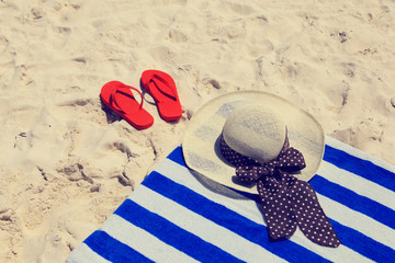 Straw hat, towel and flip flops on a tropical beach