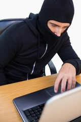 Thief with balaclava hacking a laptop