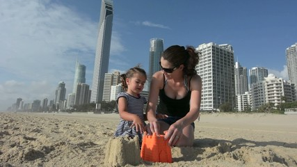 Mother and daughter builds sand castle
