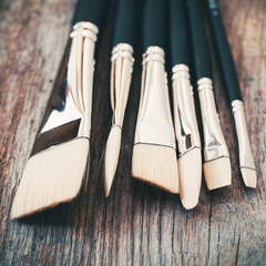 Set of artist paintbrushes closeup on rustic wooden table.