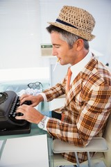 Vintage man in straw hat typing on typewriter