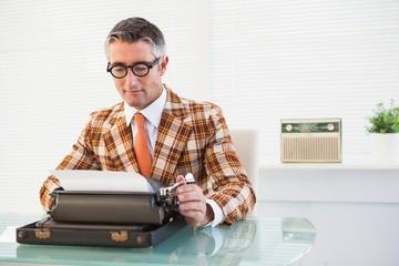 Smiling vintage man using typewriter
