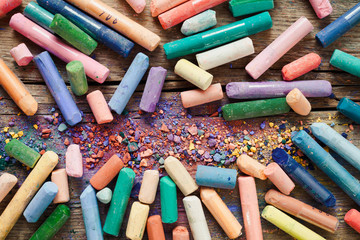 Collection of rainbow colored pastel crayons with pigment dust o