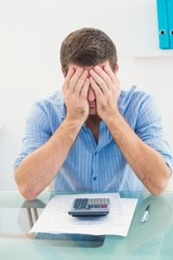 Stressed businessman covering his face at his desk
