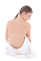 back view of beautiful woman wrapped in towel sitting isolated o