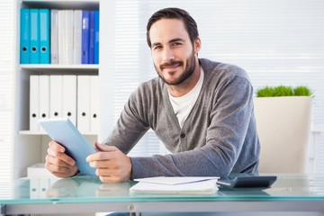 Casual smiling businessman using tablet and calculator