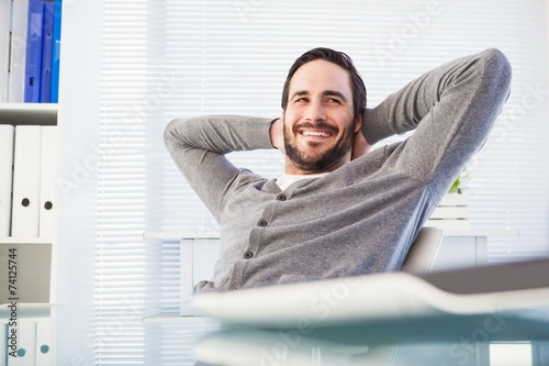 Relaxed casual businessman leaning back at his desk - 74125744