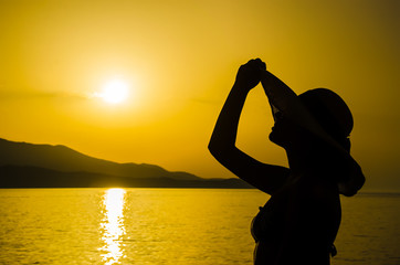 Woman on beach holding beach hat at sunset